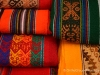 Fabric of various vibrant colors and patterns for sale in the Pisac Market in the Sacred Valley, Peru from trips around the world